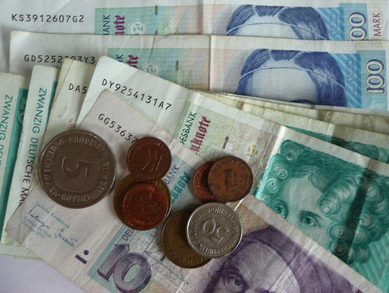 Deutsche Mark Scheine und Münzen auf einem Tisch