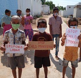 Indien: Kinder mit Stop Kinderarbeit Schildern auf Straße