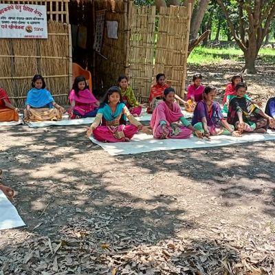 Indien: Kinder sitzen auf dem Boden und machen Yoga