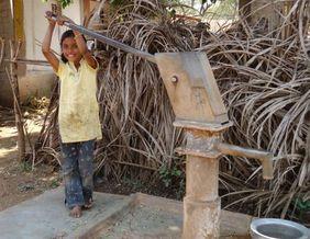Indien: Mädchen an einer Wasserpumpe. Derzeit hält eine große Wasserknappheit das Land in Atem