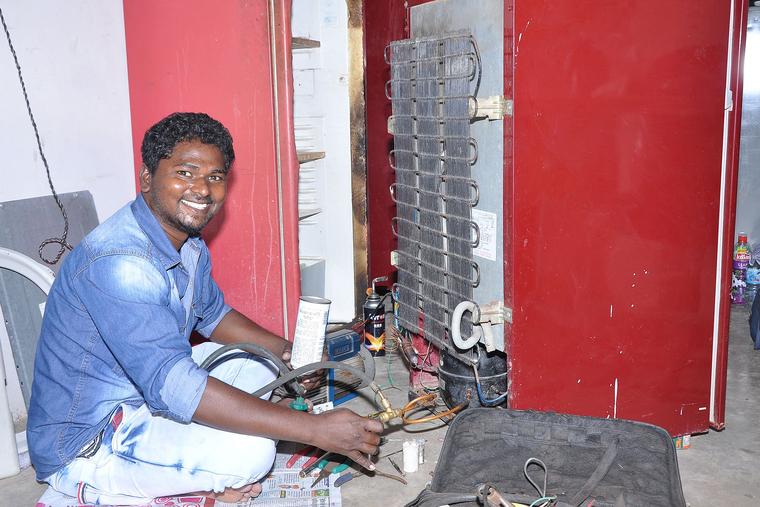 Bildung Bangladesch. Junger Mann repariert Kühlschrank