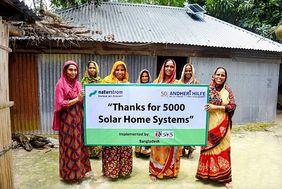 Frauen in Bangladesch vor einem Haus mit Plakat in der Hand